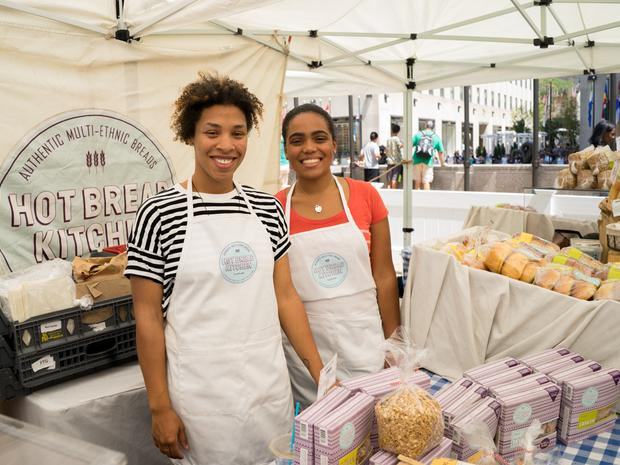 Two Hot Bread Kitchen employees smile behind their stand at the farmers market.