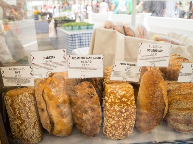 A close up of six different types of breads on display at Hot Bread Kitchen's stand at the farmers market.