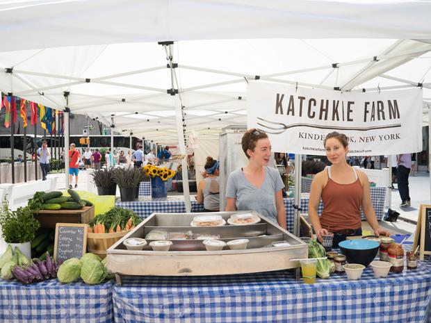 Two female Katchkie Farm employees stand behind their stand at the farmers market.