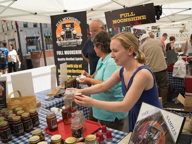 A young woman offers a free sample of moonshine at the Full Moonshine stand at the farmers market.