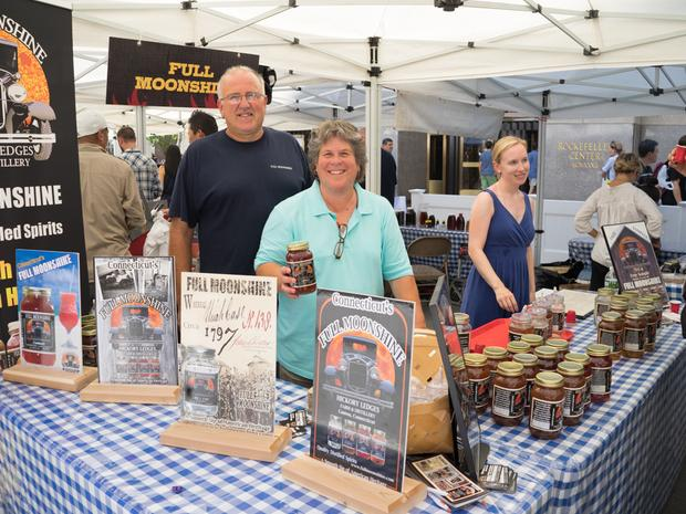 An older couple stands behind the Full Moonshine stand at the farmers market.