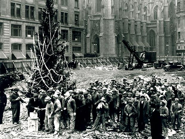 Construction workers line up for pay beside the first Rockefeller Center Christmas tree in New York in 1931.