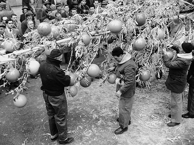 Men and women in coats decorate the Rockefeller Christmas Tree with giant ornaments in 1949.