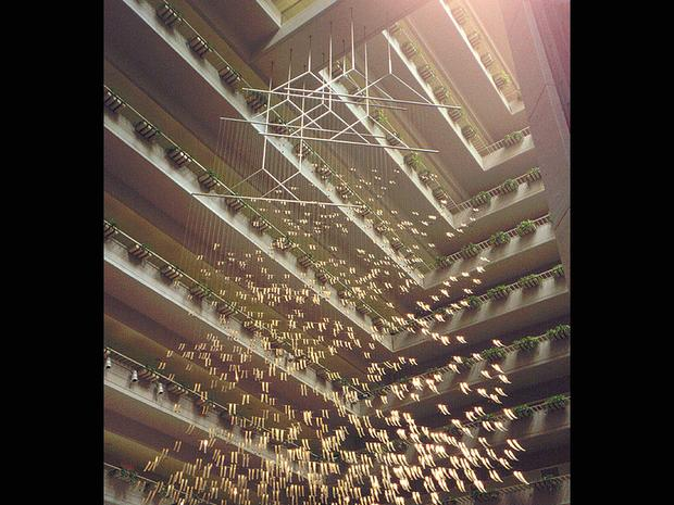 A photo of Ihara's suspended sculpture made of gold plated brass and stainless steel from the Pavilion Inter-Continental Hotel in Singapore, made by John Portman.