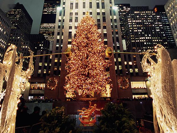 In 1999, from the point of view of the trumpt playing angels on the Rockefeller Plaza, the Christmas tree sits, lit, before the Plaza.