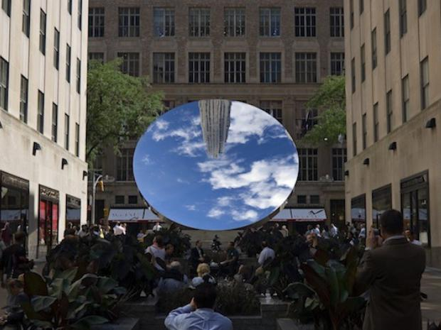 """Anish Kapoor's """"sky mirror"""" is shown here, made of polished stainless steel and displayed at Rockefeller Center at the entrance to the Channel Gardens."""