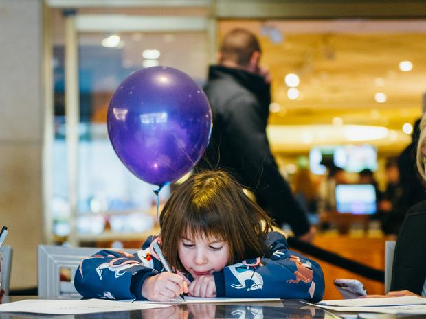 A young child instensely drawing, while a purple balloon is tied to their chair.