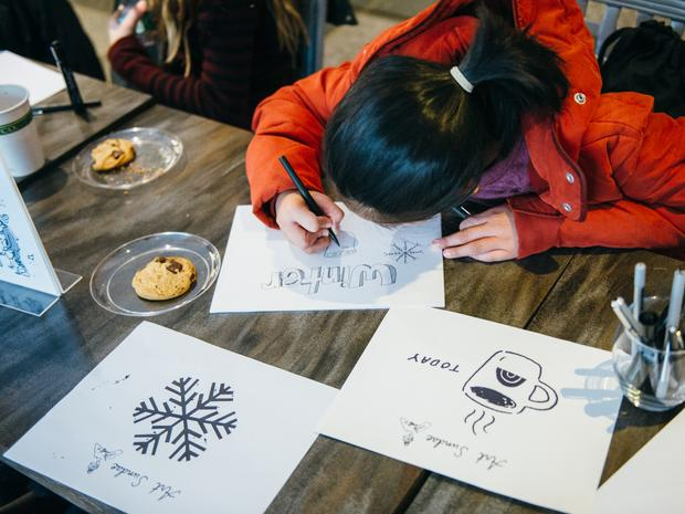 A young girl draws winter-inspired drawings at Art Sundae event.