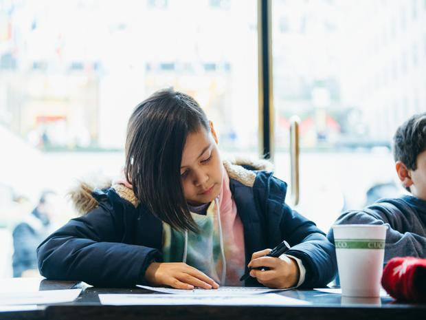 A young child drawing a picture at the Art Sundae event.