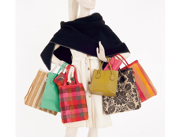 A white manikin holding six colorful tote bags, each a different design.