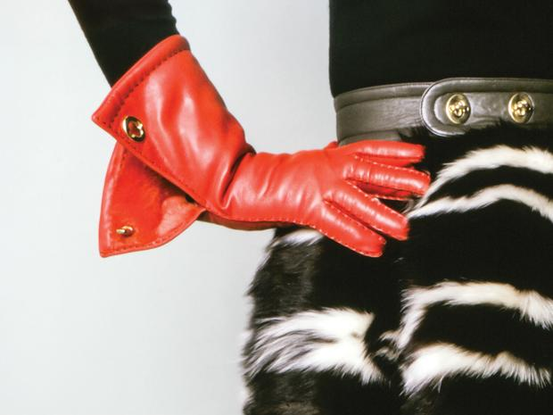 An extreme close up of a model's hand on her hip, wearing a red leather glove.