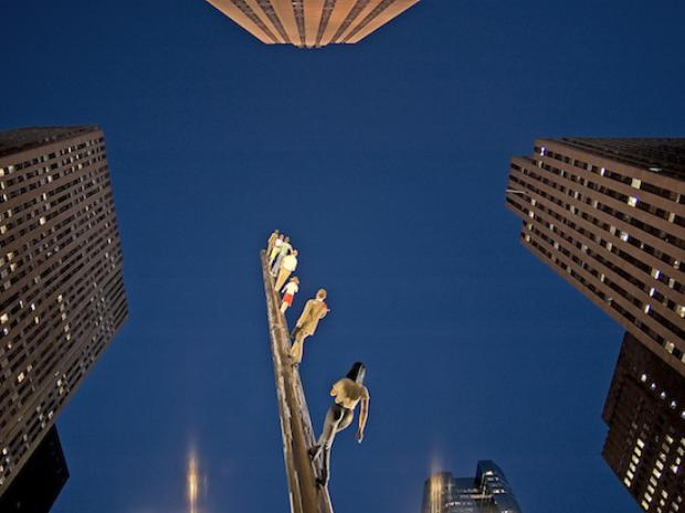 A photo from below Jonathan Borofsky's installation entitled Walking to the Sky, which exhibits realistic human figures walking toward the sky upwards of 100 feet.