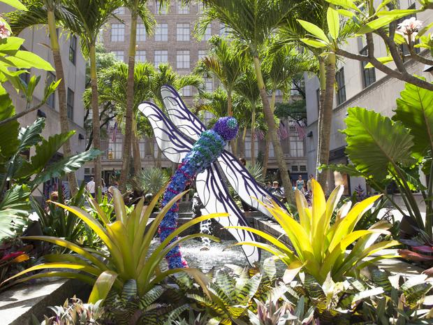 A scultpure butterfly in the Channel Gardens at Rockefeller Center surrounded by different plants and leaves.