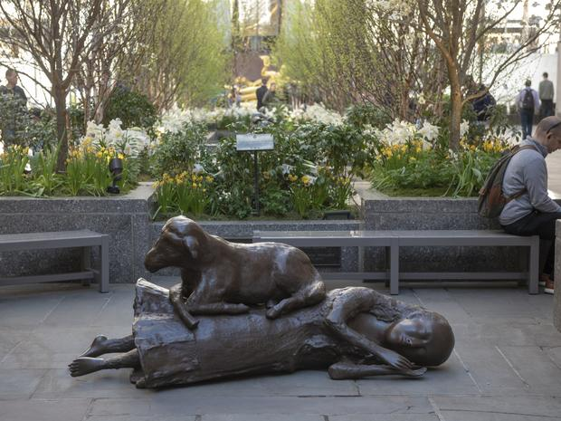 A close-up of Kiki Smith's sculpture showcased outside Rockefeller Center entitled Rest Upon, which is a life-sized bronze sculpture of a lamb on top of a sleeping woman.