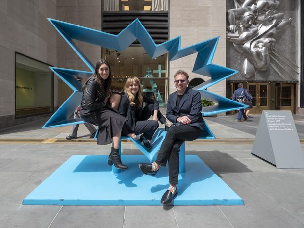 Three visitors pose upon a blue vector-shaped statue.