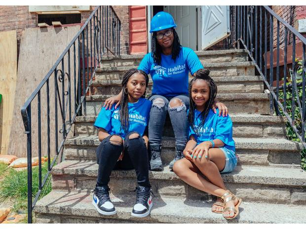 A woman and two girls sitting on the stepsof the building they were working in while wearing Habitat for Humanity tee shirts.
