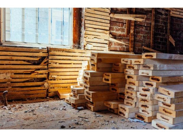 A photo of piles of wood layered on top of one another inside the Habitat for Humanity project.