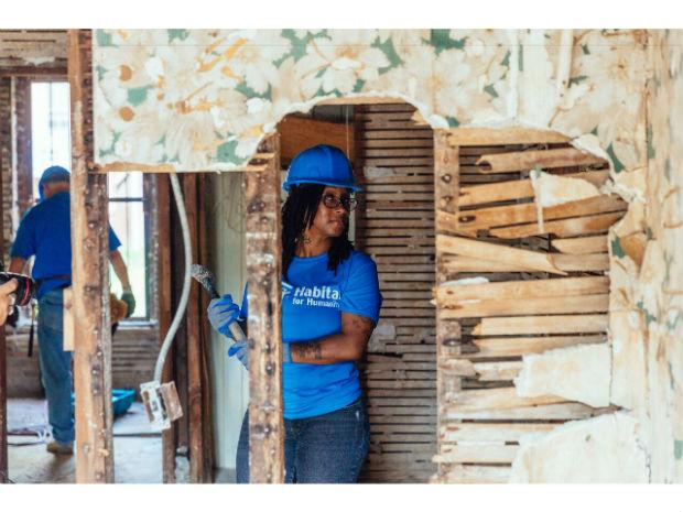 A photo of a woman through the torn down wall holding a hammer, while wearing a hard hat and Habitat for Humanity tee shirt.