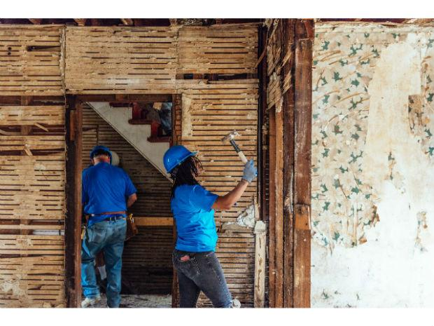 A photo of a woman inside the Habitat for Humanity project hammering the wall.