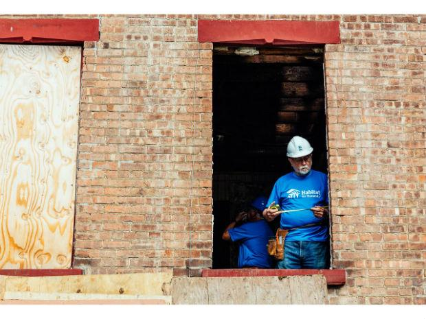 A photo taken of a man measuring through an open window from the outside of the Habitat for Humanity project.
