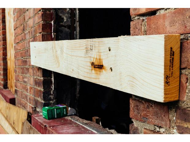 """A piece of wood across a brick wall with a view of the words, saying """"85th Rockefeller Center Tale Lighting."""""""