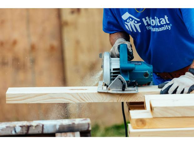 A close-up of a man slicing through the Rockefeller Christmas tree wood, wearing a Habitat for Humanity tee shirt.