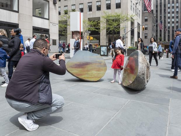 A father photographing his small daughter, who poses in between split stones.