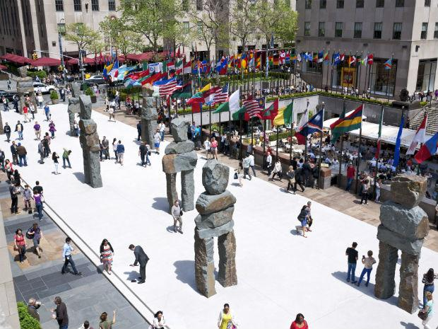 Ugo Rondinone's sculpture entitled Human Nature on display at Rockefeller Center while people walk around the grounds outside.