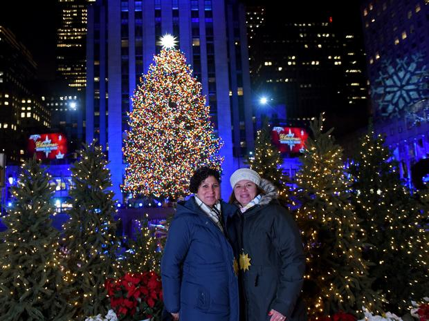 Lissette Gutierrez, left, and Shirley Figueroa, of Wallkill, NY, pose in front of the tree they donated to serve as this year's Rockefeller Center Christmas tree