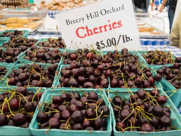 A close up of Breezy Hill Orchard cherries on display at the farmer's market.