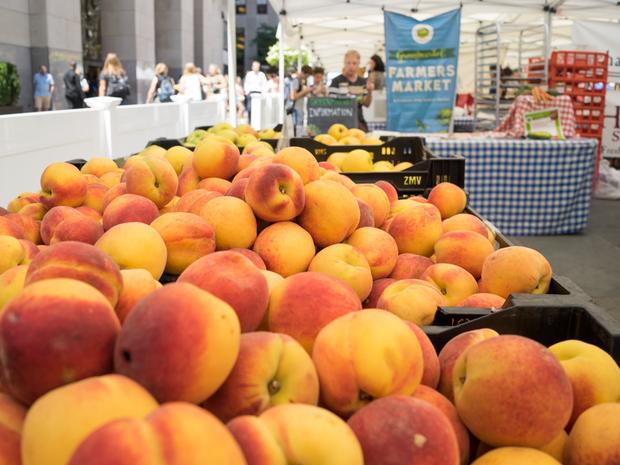 A close-up of beautiful, ripe, orange peaches in cases at the Rockefeller Center Greenmarket.
