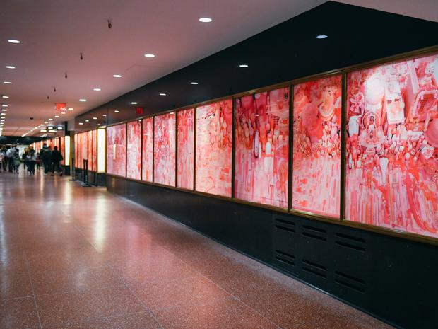 A hall with Pink Project portraits lining the wall.