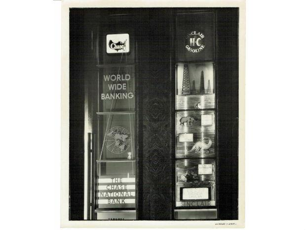 A close-up black and white photo of commercials for Chase National Bank and Sinclair gasoline in the Rockefeller Center lobby.